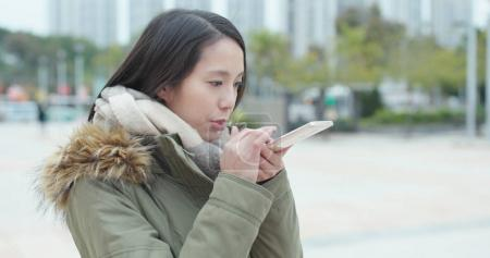 Woman sending audio message on cellphone at outdoor