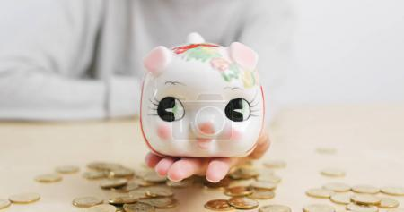 Woman holding piggy bank with coin on the desk