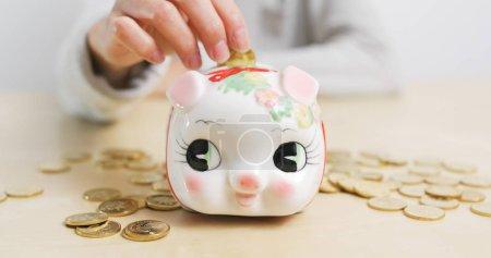 Woman putting golden coins into piggy bank
