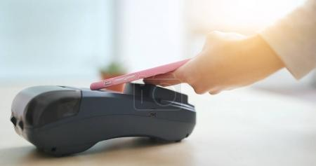 Woman pay by mobile phone with NFC