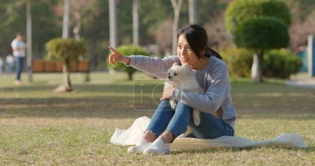 Cute Pomeranian dog with pet owner with outdoor park