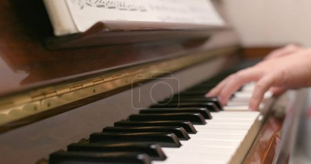 Playing piano at home close up