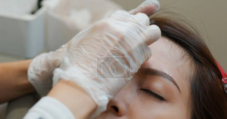 Photo pour Spécialiste de l'esthéticienne du maquillage permanent faisant maquillage microblading sourcil maquillage - image libre de droit
