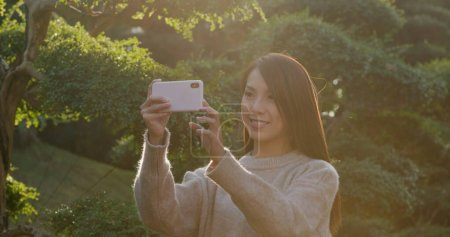 Photo for Woman take photo on cellphone at sunset - Royalty Free Image