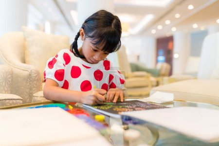 Photo for Kid girl concentrate draw on book - Royalty Free Image