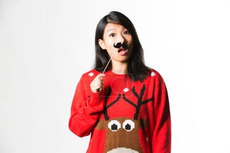 Mujer en jersey de Navidad con bigote falso
