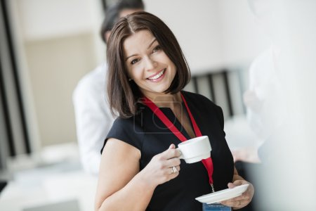 Happy businesswoman with cup of coffee