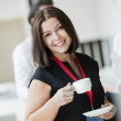 Portrait of happy businesswoman holding coffee cup...