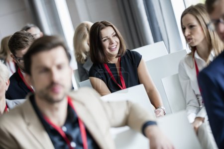businesswoman sitting with colleagues in seminar hall
