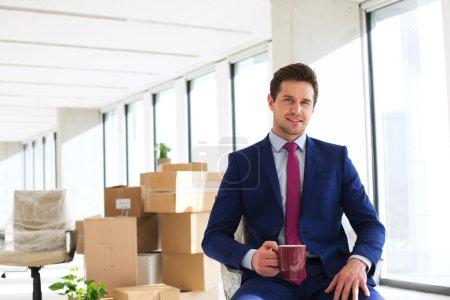 Photo pour Vue de face du jeune homme d'affaires ayant café sur chaise au nouveau bureau - image libre de droit
