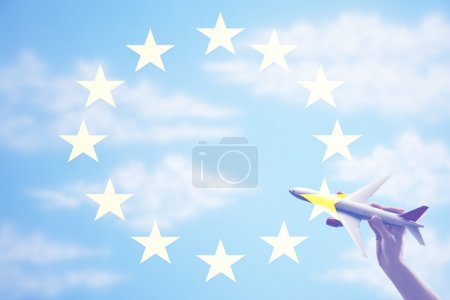 toy plane flying in from of EU Flag