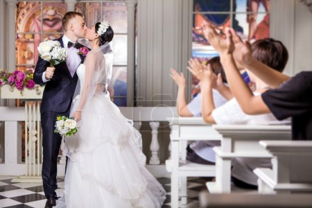 Wedding guests applauding newlywed couple