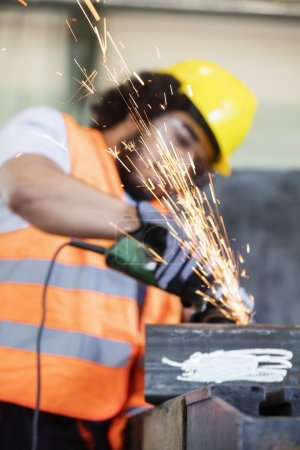 Sparks coming out from grinder with worker