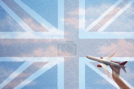 Photo pour Avion jouet volant devant drapeau Union Jack - image libre de droit