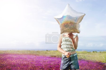 Photo for Front view of preadolescent girl holding star shaped balloon in front of her face while standing at flower field - Royalty Free Image
