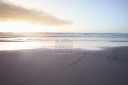 Ocean and arrow sign on beach in sunshine
