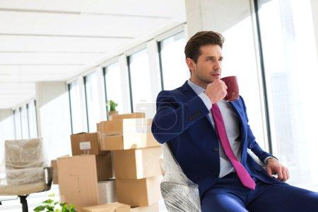 Photo pour Vue de côté du jeune homme d'affaires ayant café sur chaise au nouveau bureau - image libre de droit