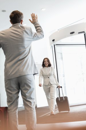 Businesswoman with luggage walking towards colleague