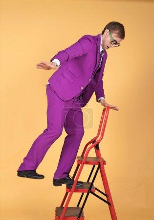 Stylish man falling off ladder