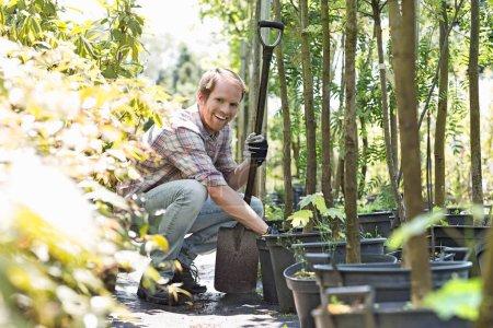Happy gardener holding shovel