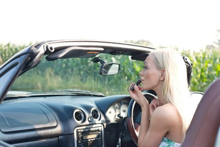 woman applying lipstick in convertible
