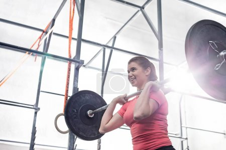 smiling woman lifting barbell