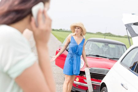 women standing by damaged cars