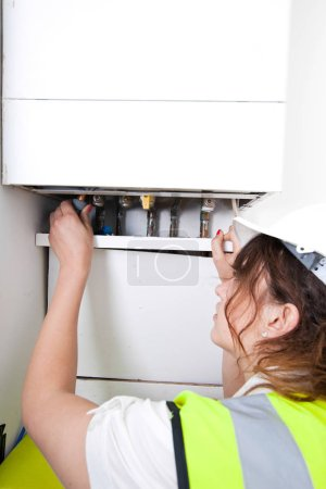 plumber servicing central heating boiler