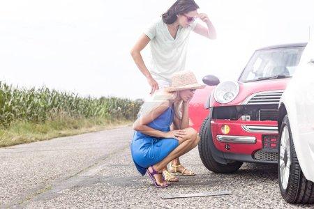 Tensed women looking at damaged cars