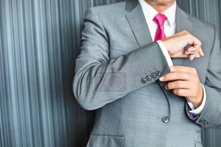 Mature businessman buttoning sleeve