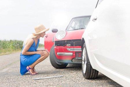 woman looking at damaged cars