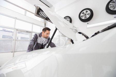 automobile mechanic examining car engine