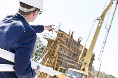 Architect holding blueprints while pointing