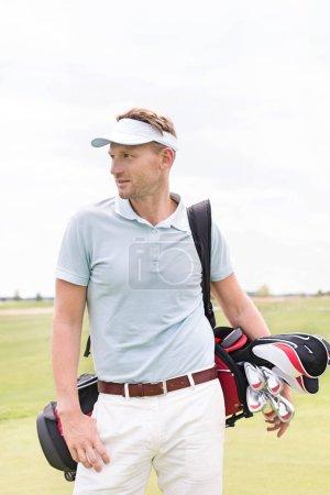 Thoughtful man carrying golf bag