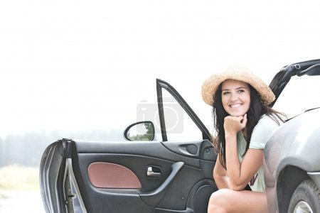 Happy woman sitting in convertible