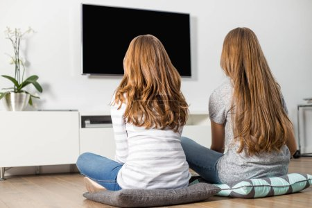 Siblings watching TV at home