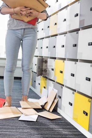Businesswoman standing by fallen documents