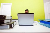 Man poking out over laptop