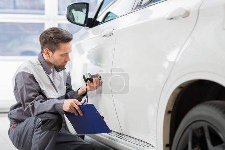repair worker examining car paint