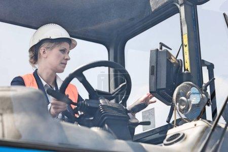 Female worker operating forklift truck