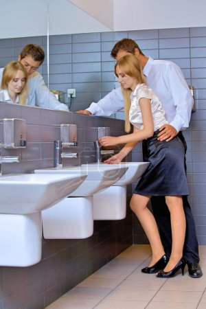 Business couple flirting in office washroom