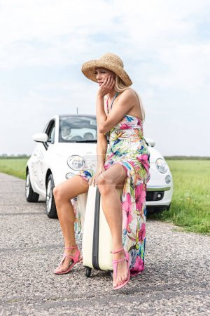 Photo for Irritated woman sitting on luggage by broken down car on country road - Royalty Free Image