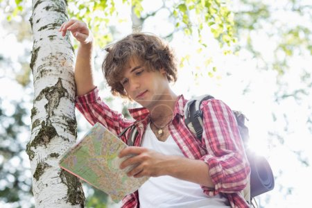 Male backpacker reading map