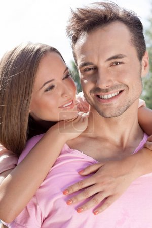 woman embracing man from behind in park