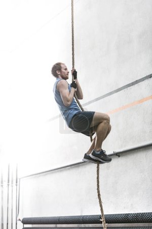man climbing rope in crossfit gym