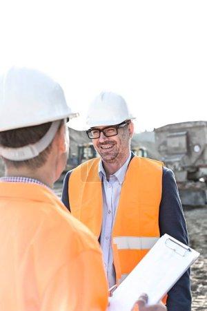 Photo pour Des ingénieurs heureux discutent sur le chantier contre un ciel dégagé - image libre de droit