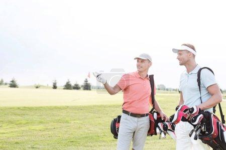 Photo pour Homme montrant quelque chose à un ami au parcours de golf dans le ciel clair - image libre de droit