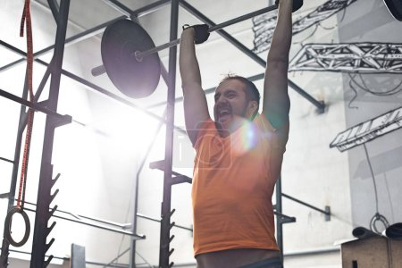 man lifting barbell in crossfit gym