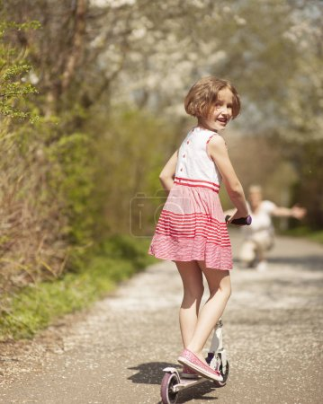 Young girl riding scooter