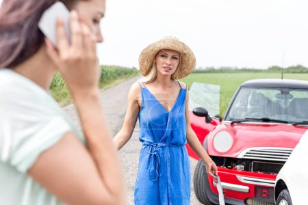 Photo for Angry woman looking at female friend using cell phone by damaged cars on road - Royalty Free Image